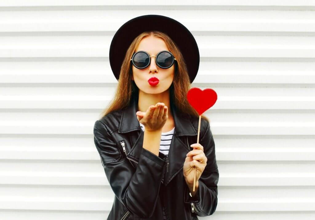 Mulher mandando um beijo com as mãos. Ela usa um chapéu e uma jaqueta, ambos da cor preta e segura um coração vermelho em uma das mãos.