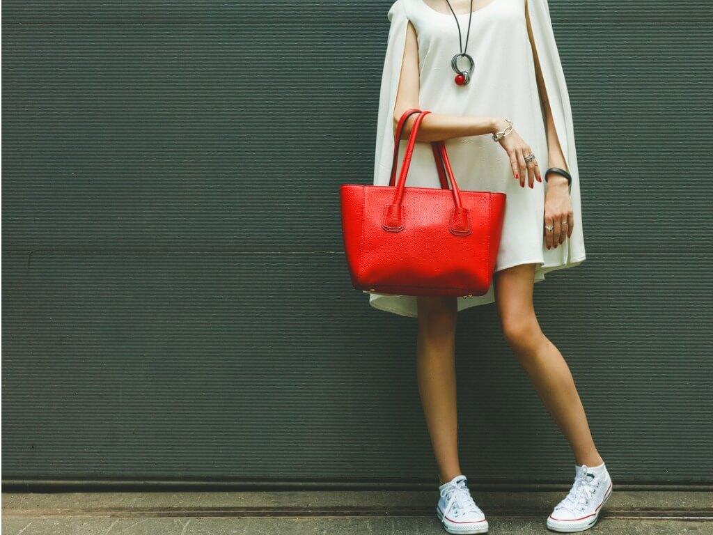 Imagem de uma mulher do pescoço para baixo usando um vestido branco e uma bolsa vermelha